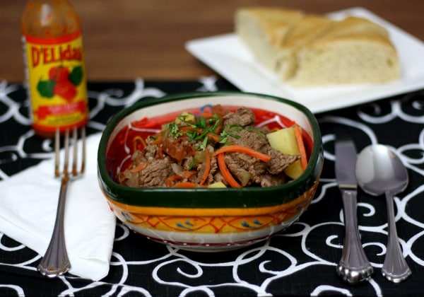 a colorful bowl of beed stew on a black and white placemat with cutlery on either side and a plate of bread in the back