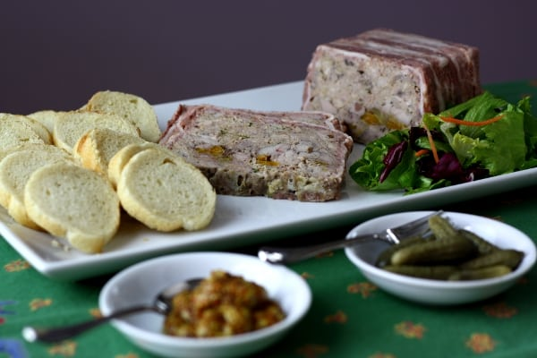 terrine de campagne on a plate with baguette slices and bowls of mustard and cornichons in the front