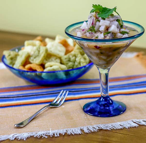 ceviche made with tilapia in a martini glass with a blue bowl of veggie chips in the back