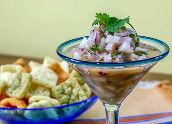 a martini glass filled with tilapia ceviche and a bowl of veggie chips in the back