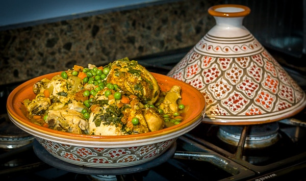 an orange tagine on a stove filled with chicken, peas, and herbs with the lid aside
