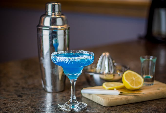 a blue margarita in a glass with a metal shaker in the back and a cutting board with lemons on the right