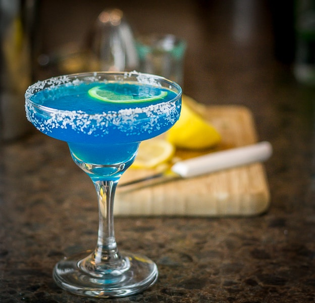 a blue margarita in a salted glass with a slice of lemon