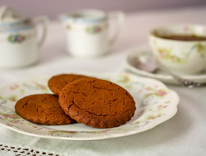 old fashioned cinnamon cookies on an antique plate with a cup of tea in the background