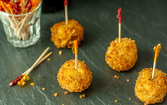 four croquetas with toothpicks with a glass of toothpicks on the left