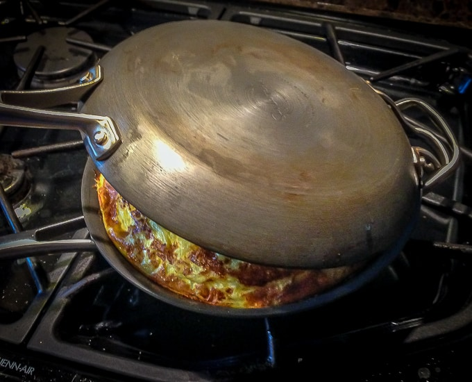 a tandem pan on a stove with a tortilla inside