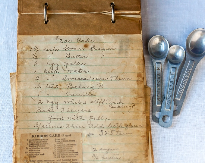 an old recipe notebook written in fountain pen with measuring spoons on the right