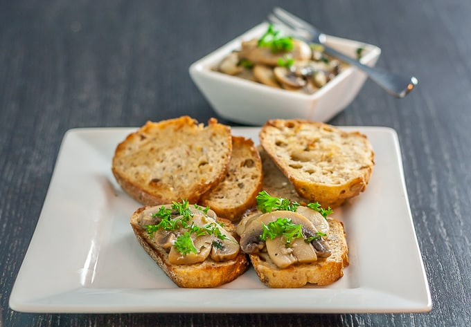 a white plate with toasted baguette and mushrooms, a bowl of mushrooms in the background