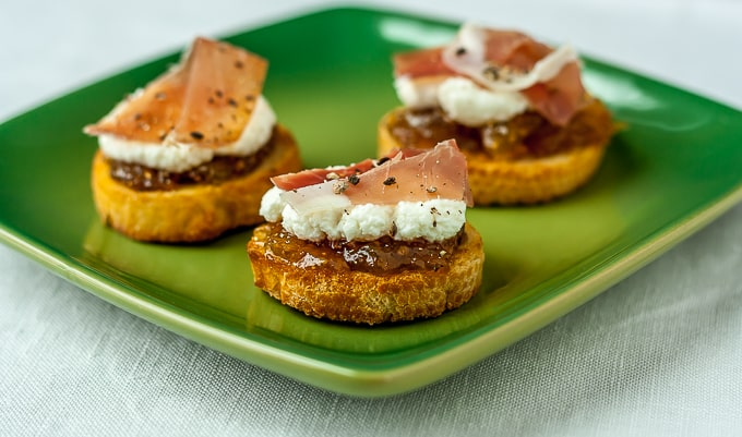 italian appetizers with bread, figs, ricotta, and prosciutto