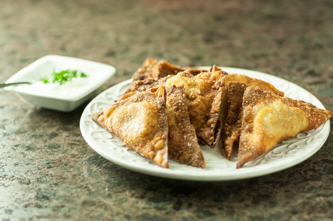 a white plate of fried samosas with sauce on the left