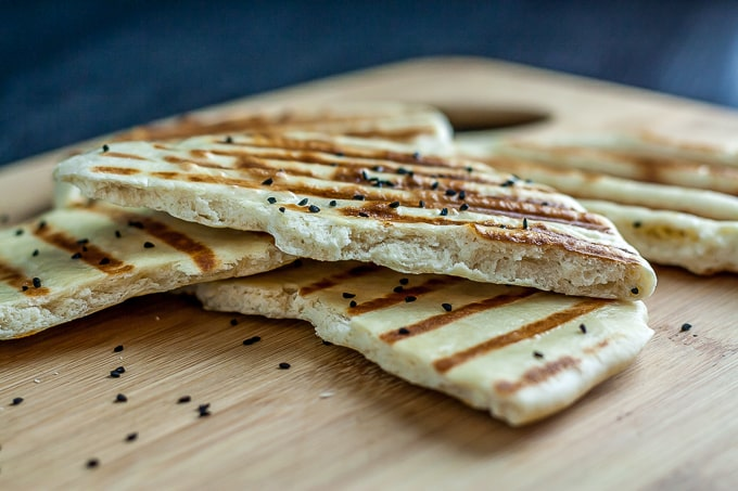 grilled naan on a wooden cutting board with black sesame seeds