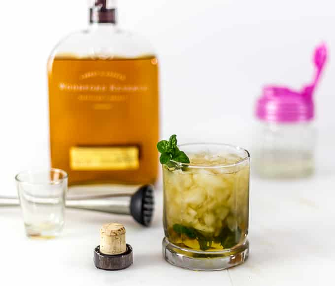 a mint julep in a glass next to a cap with bourbon, a muddler, and a shot glass in back