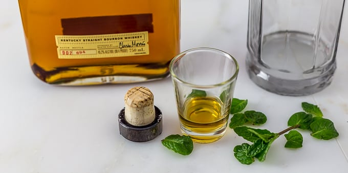 mint leaves, a shot glass with bourbon, and a cap with bourbon and a glass in back