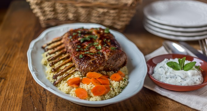 Turkish Rack of Lamb on a plate with cous cous and yogurt in a bowl on the right