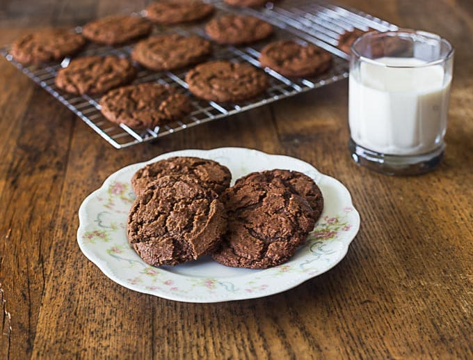 four chocolate cookies on an antique plate with a glass of milk on the right and a drying rack of cookies in the back