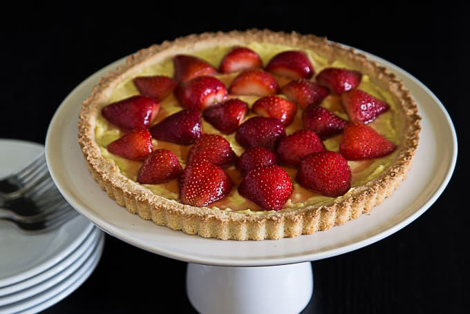 a large strawberry tart on a cake riser with a stack of plates and cutlery on the left