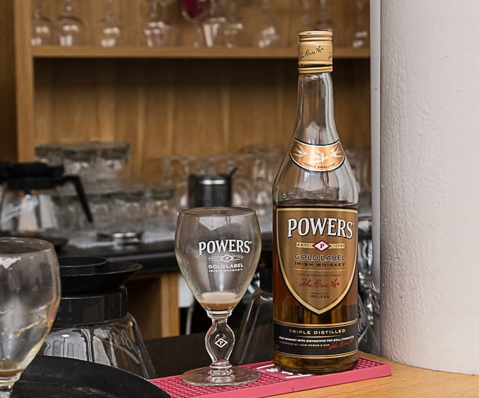 Powers Irish whiskey bottle and a glass on a bar