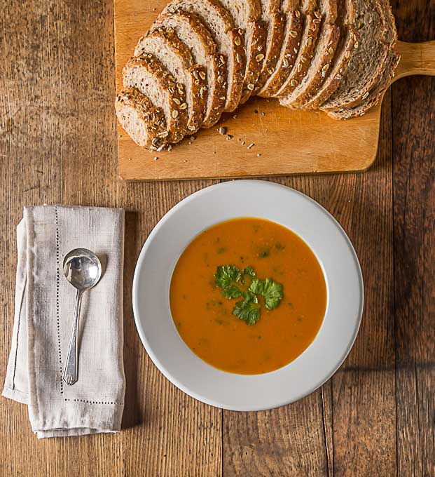 a bowl of carrot coriander soup with a spoon and napkin on the left and a loaf of multigrain bread above