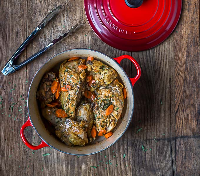 chicken tarragon in a red dutch oven with tongs and the lid above