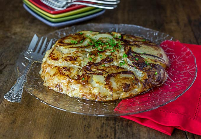 An italian potato pancake with onions on a plate with a fork and a red napkin underneath