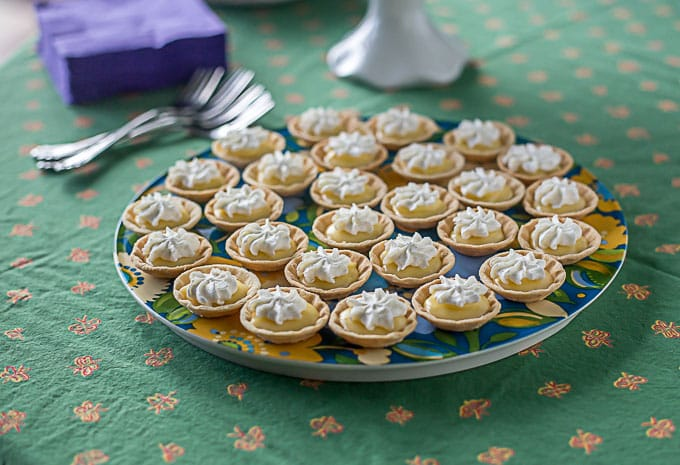 a colorful plate of mini lemon tarts with whip cream on a green tablecloth