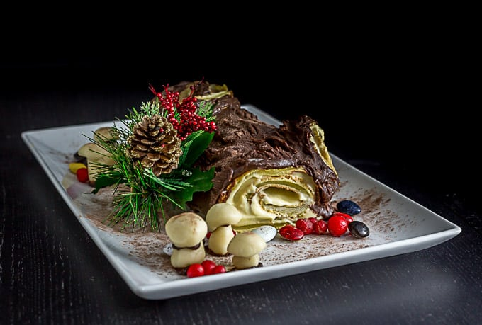 a French buche noel on a plate with marzipan berries, mushrooms, and some tree garnish