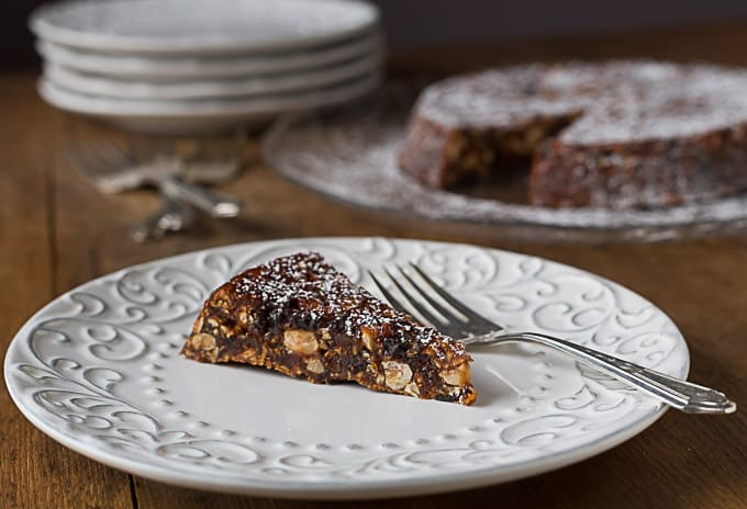 a slice of italian panforte on a white plate with a fork with the full cake in the back