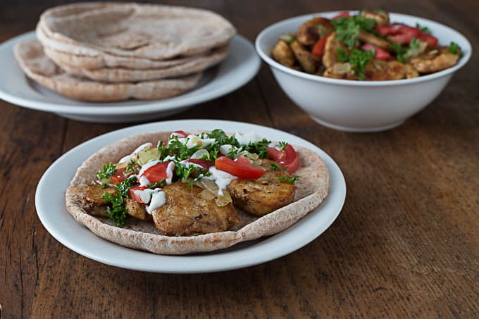 a wheat pita with chicken shawarma topped with parsley, yogurt, and tomatoes with serving dishes in the back