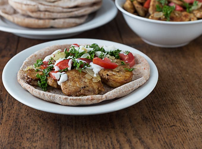 chicken shawarma on a pita topped with parsley, tomatoes, and yogurt