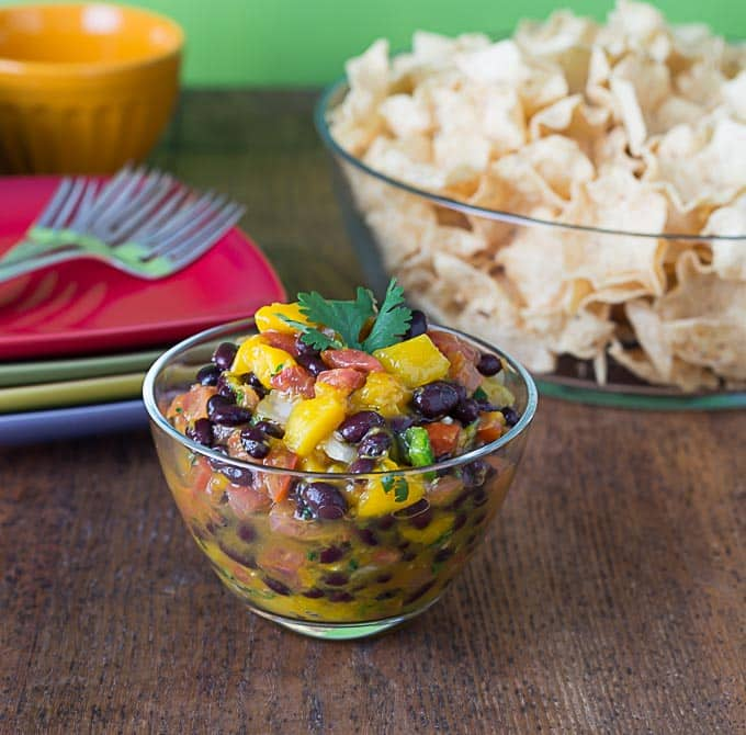 a closeup shot of mango black bean salsa with a bowl of chips in the background