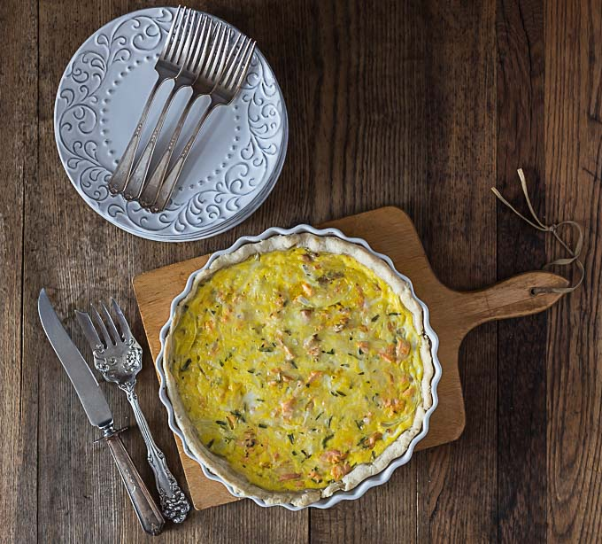 a salmon quiche on a cutting board with serving cutlery on the left and a stack of plates and forks above