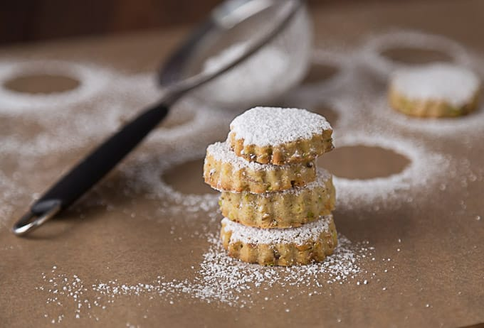 a stack of pistachio rosewater cookies with powdered sugar