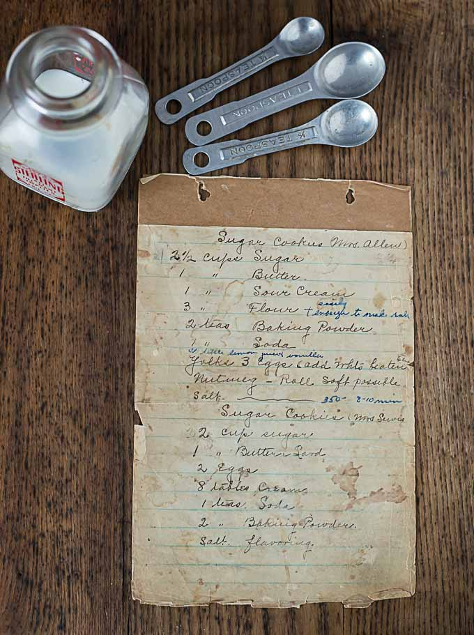 a page of an old recipe book with metal spoons and a glass cream container above