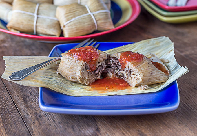 A tamale on a blue plate with red salsa.