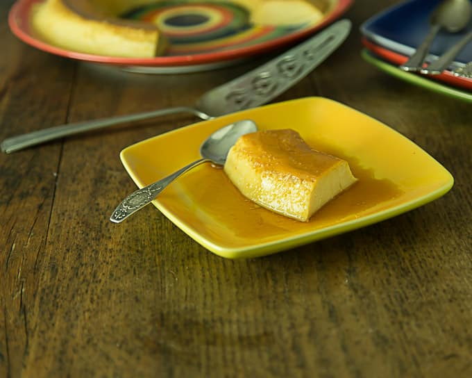 a yellow plate with a slice of no bake flan and a spoon with a cake knife in the back