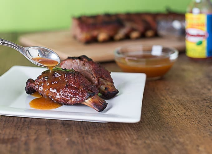 mango habanero ribs on a white plate with a spoon pouring sauce