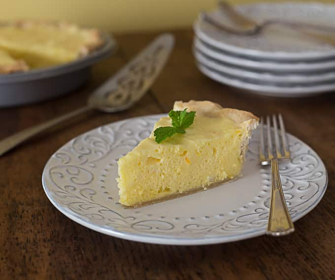 light and fluffy orange lemon pie on a white plate with a fork
