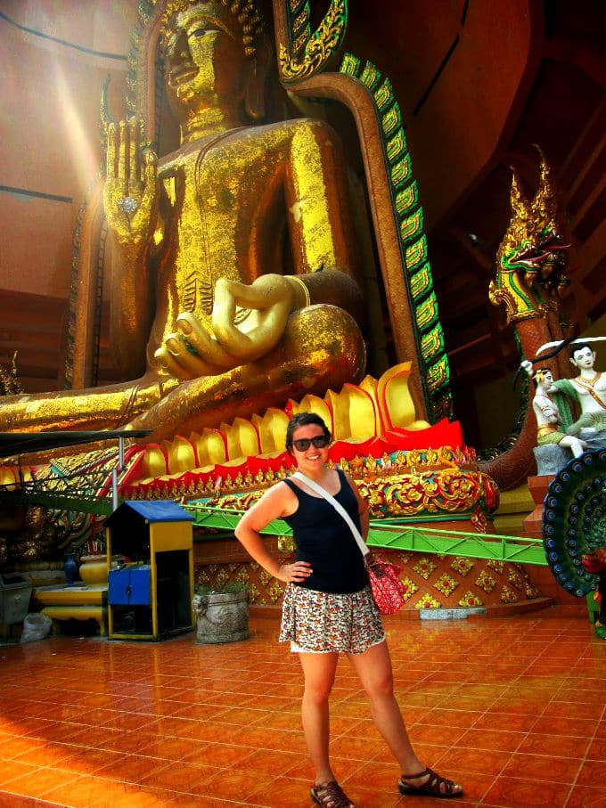 a girl in front of a golden Buddah statue in Thailand
