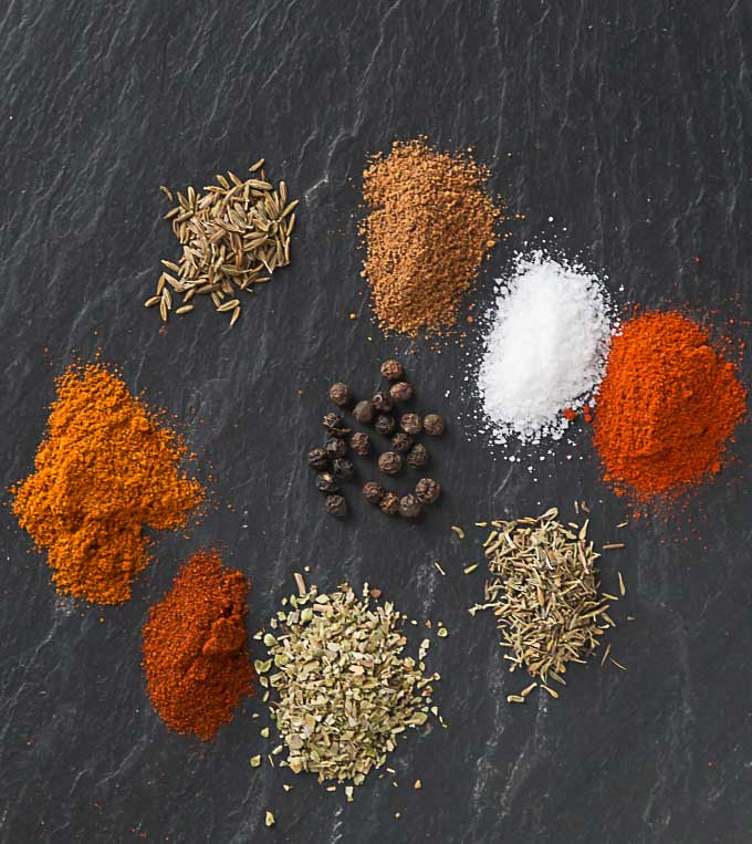 nine colorful piles of spices arranged in a circle on a black slate