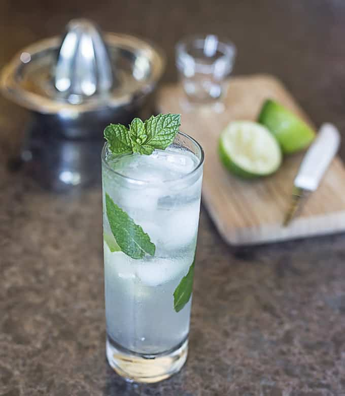 a tall glass with coconut mojito and mint leaves with a cutting board, limes, and a juicer in the back