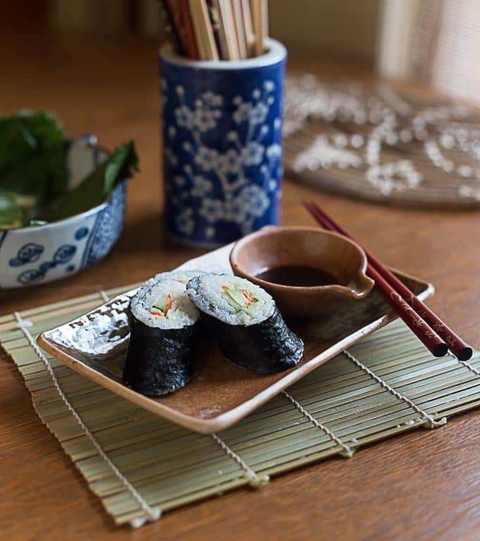 three pieces of sushi on a plate with soy sauce and chopsticks