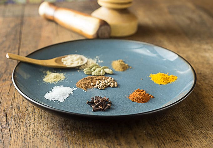 A blue plate with spoon along with spices to make a curry powder blend.