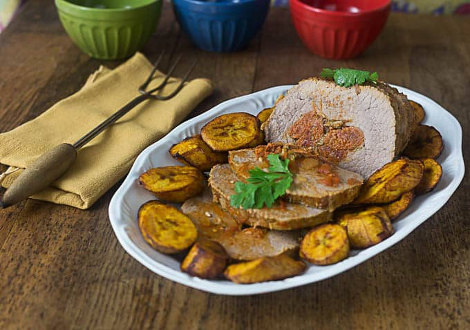 a plate of roasted, sliced, stuffed pork with fried plantains and a yellow napkin and poker on the left