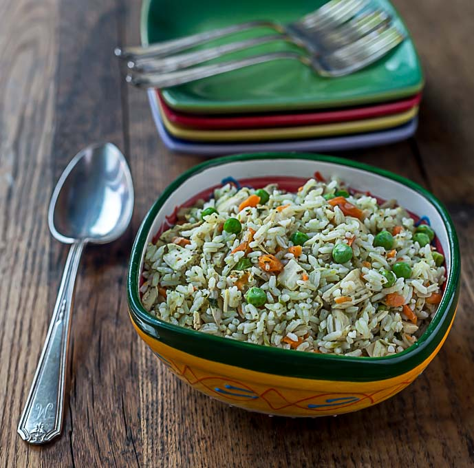 a bowl of rice with peas, turkey, and carrots on a wooden table with a spoon on the left