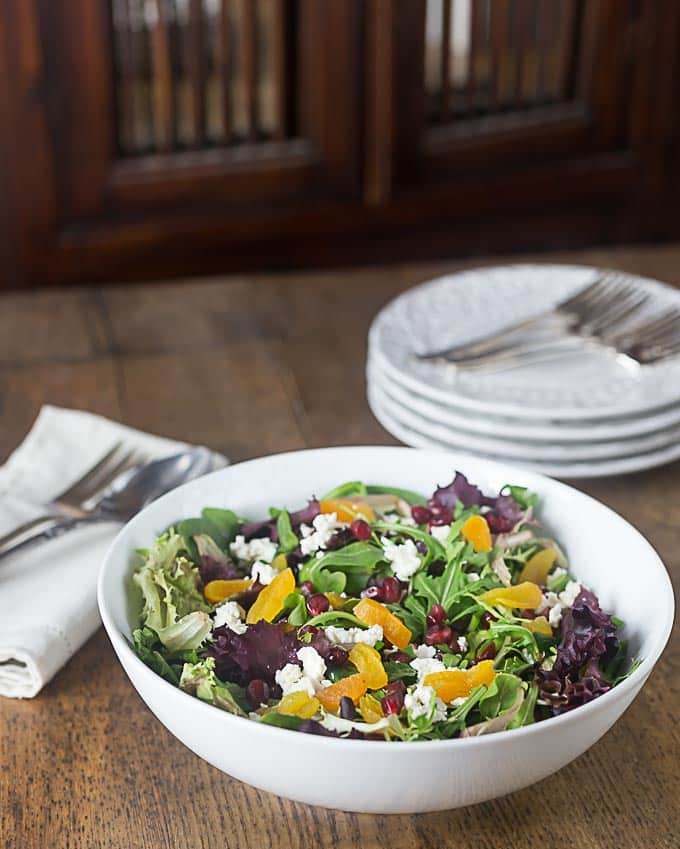 a white bowl of salad with purple lettuce, apricots, and feta cheese with a stack of plates in the back