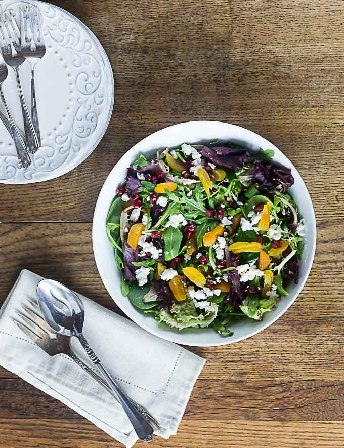 an upward view of a salad bowl with apricots, purple lettuce, and feta cheese