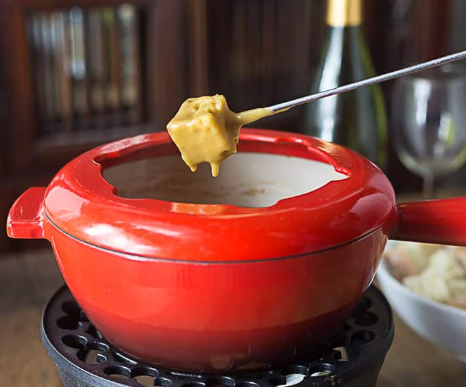 a red fondue pot with a fondue fork dipped in bread and cheese