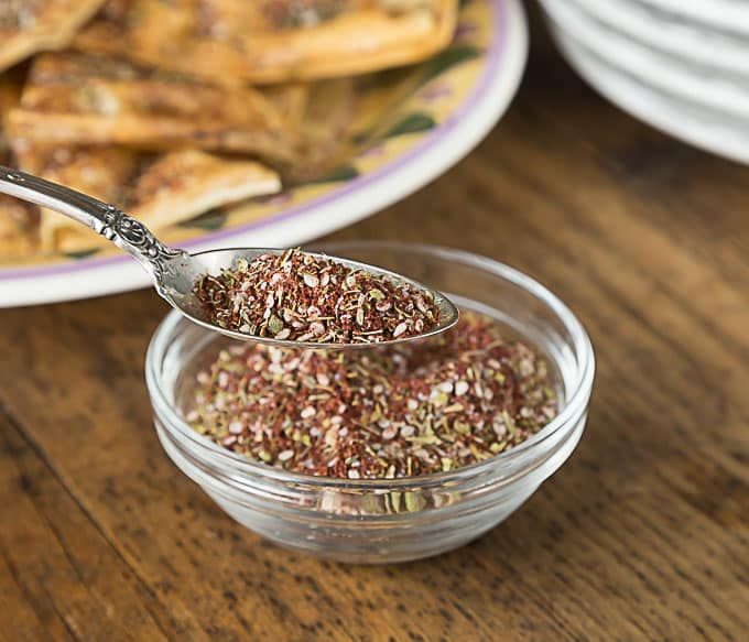 a spoon with zatar and a bowl of zatar