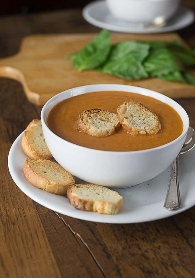 a bowl of tomato bisque with slices of baguette and sliced baguette on the side