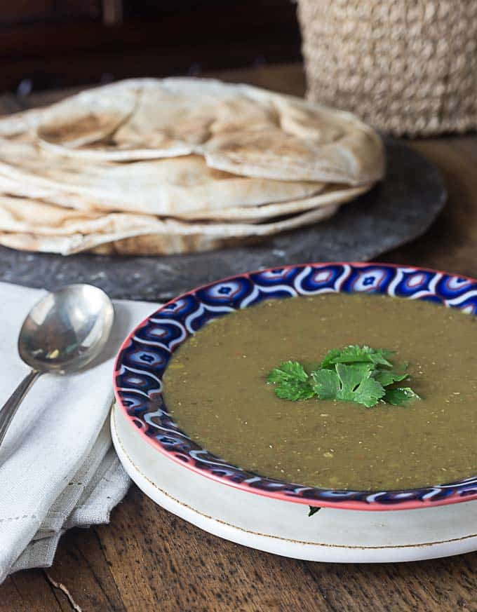 a bowl of middle eastern lentil sop with a spoon on the left and naan in the back